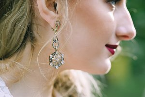 Vintage earring on the bride's ear. Close-up portrait of the bride. Artwork.