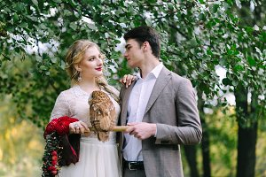 The owl sits on the girl's hand. The bride and groom with the owl.