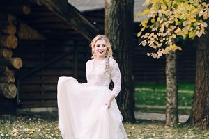Happy bride is posing in fluttering dress on nature. Artwork