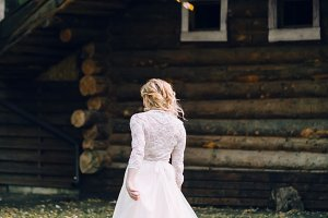 Blonde bride is walking in fluttering dress on wooden house background. Back view. Artwork
