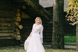 Happy bride with curly blonde hair pose next to the wooden house back. Rustic wedding