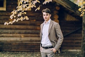 The handsome groom stand next to the wooden house. Autumn wedding. Outdoors