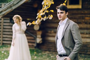 The handsome groom stand at the on blurred bride background. Autumn wedding. Outdoors