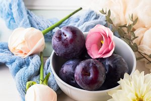 Blue plums in bowl with flowers