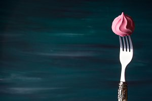Pink meringue on fork on dark green
