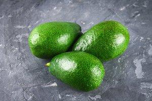 Three greens raw raw ripe avocado fruits on a gray dark concrete table.