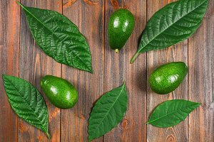 Three green raw ripe avocados with leaves lie on a wooden brown table. Flat lay. Top view.