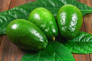 Three green raw ripe avocados with leaves lie on a wooden brown table.