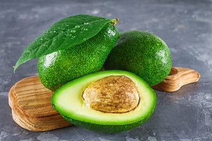 Three green raw ripe avocado fruits and a cut half with a bone with leaves on a wooden cutting board on a gray dark concrete table