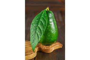 A green raw ripe whole avocado fruit with a leaf is on a cutting board on a wooden brown table.