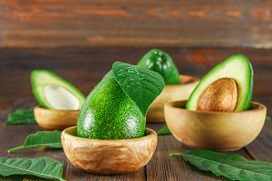 Green raw ripe cut and whole avocado fruits with stone lie in wooden bowls surrounded by leaves on a brown table.