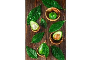Green raw ripe cut and whole avocado fruits with stone lie in wooden bowls surrounded by leaves on a brown table. Flat lay. Top view.