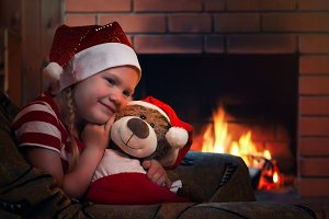 A happy girl and a plush bear. Evening at home, a comfortable armchair and fireplace