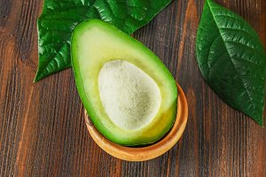 A green, raw, ripe, avocado-cut fruit without seeds lies in a wooden bowl, surrounded by leaves on a brown table.