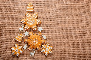 Christmas tree made of gingerbread cookies homemade and New Year decor on burlap backgraund. Merry Christmas postcard. Free space