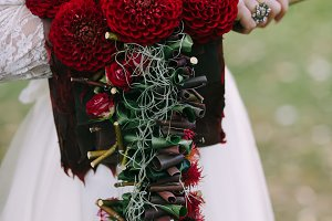 Bouquet with bordeaux dahlias on bride hand. Wedding decoration. Flowers dahlias.