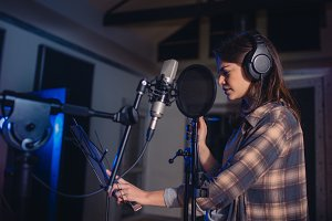 Woman recording music in studio
