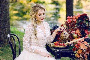 The bride with the owl. Beautiful smiling bride is sitting near the served wedding table with red autumn leaves