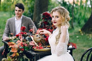 The bride with the owl on blurred groom background. Autumn wedding