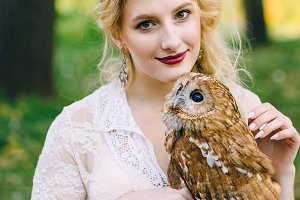 The owl sits on the girl's hand. The bride with the owl.