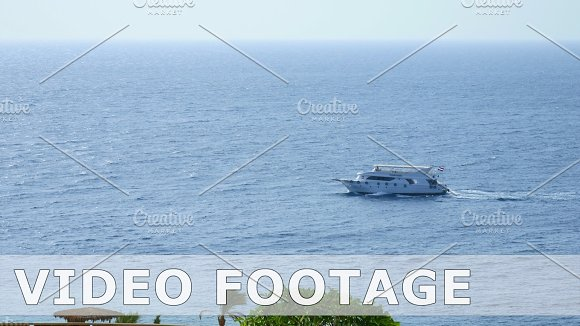 Powerboats and ship sails along tropical sea