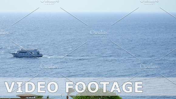 Powerboats and ship sails along tropical sea in Graphics