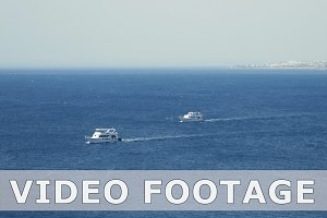 Powerboats and ship sails along tropical sea
