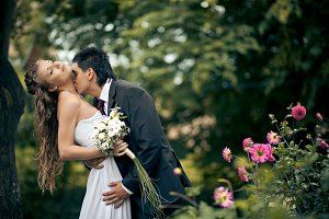 Groom bends curly bride and kisses