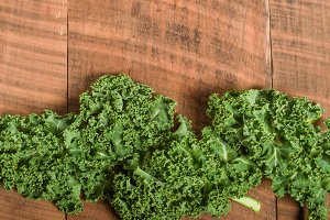 Curly green kale on wooden table