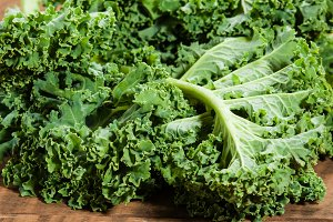 Green curly kale on table