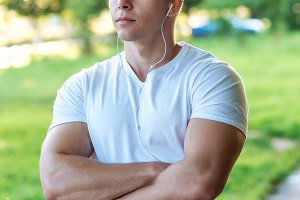 The man atlen stands in the park with headphones, a white T-shirt. Summer lifestyle, motivation is strong. Muscular arms.
