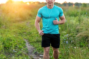 Athlete in a T-shirt and shorts runner in the evening, jogging. Happy smiling summer lifestyle, motivation strong. Outdoors in the park. A man in the park listens to an audiobook, a confident look.