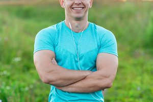 Happy man in the park wearing headphones smiling, concept of happiness. Summer lifestyle is outdoor recreation, motivation is strong. Close-up of muscular arms.