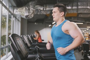 Strong man in the gym - bodybuilder running on the running track in the gym