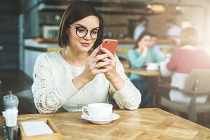 Young businesswoman in glasses and white sweater is sitting in cafe at table and using smartphone, working.E-learning