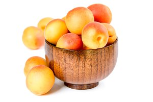 Ripe apricots in wooden bowl
