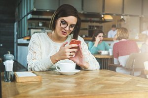 Young happy businesswoman in glasses and sweater is sitting in cafe at table and using smartphone, working.E-learning