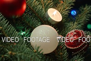 Christmas decoration, holidays and advertisement concept - close up of natural green fir wreath with a burning candle