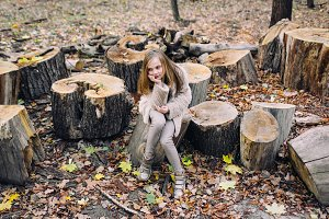 Little girl is sitting on wooden stump in the forest at autumn day.