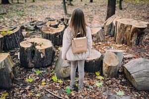 Little girl stand next to wooden stumps in the forest at autumn day.