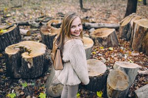 Smiling little girl stand next to wooden stumps in the forest at autumn day.