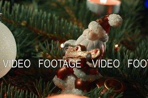 toy Santa closeup on the Christmas tree with Christmas balls and candle