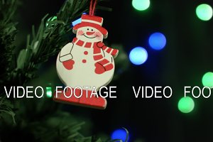 Snowman and Christmas ornaments for the Christmas tree on the background of lights