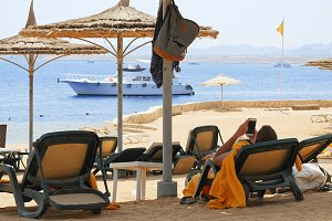 Man is lying on the beach couch under the umbrella