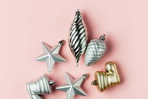 silver and gold Christmas toys isolated on a pink background
