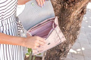Closeup woman hands with fashion luxury snakeskin python handbag. Outdoors, Bali island.