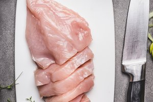 Raw chicken breast on cutting board