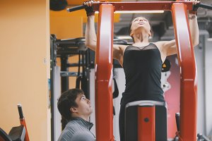 Fitness-club - young woman performs Pull-Ups with male coach