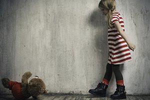 The wicked girl threw a toy bear. Background textured wall. The concept of children's resentment, the complexity of education, the child's behavior