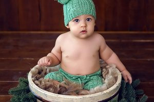 child sits in a wooden basket in green pants